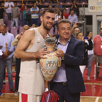 The Regional Governor of Crete, Mr. Arnaoutakis Stavros, awards the first-place trophy to the captain of Olympiacos, Vaggelis Mantzaris.