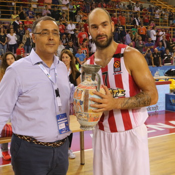 The CEO of Alfa Plus S.A. Mr. Roussakis Manolis, awards the second-place trophy to the captain of Olympiacos, Vasilis Spanoulis.